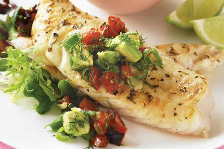 Cajun fish, avocado and grilled capsicum served on a white plate.