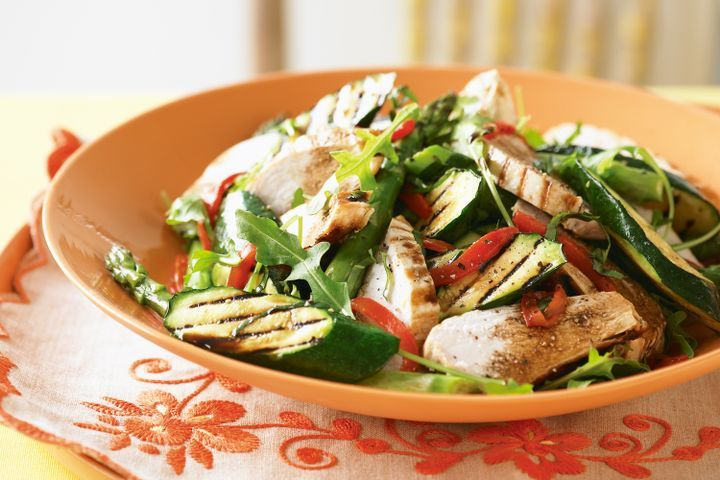 A char-grilled chicken salad with zucchini, capsicum, asparagus and rocket.