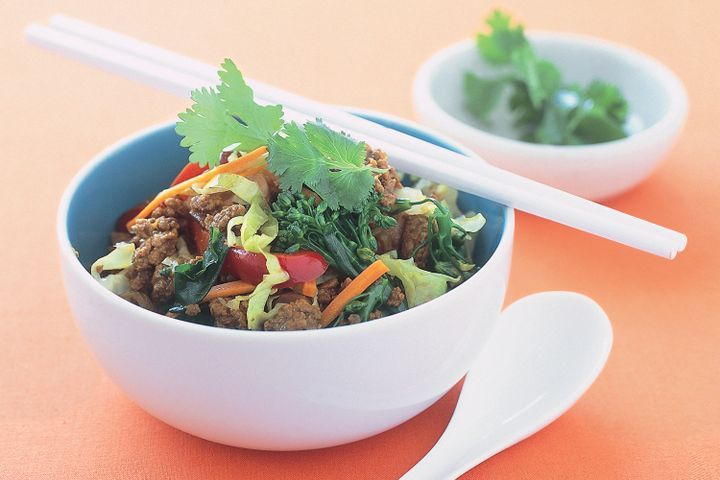 A curried beef & vegetable stir-fry freshly made in a white bowl.