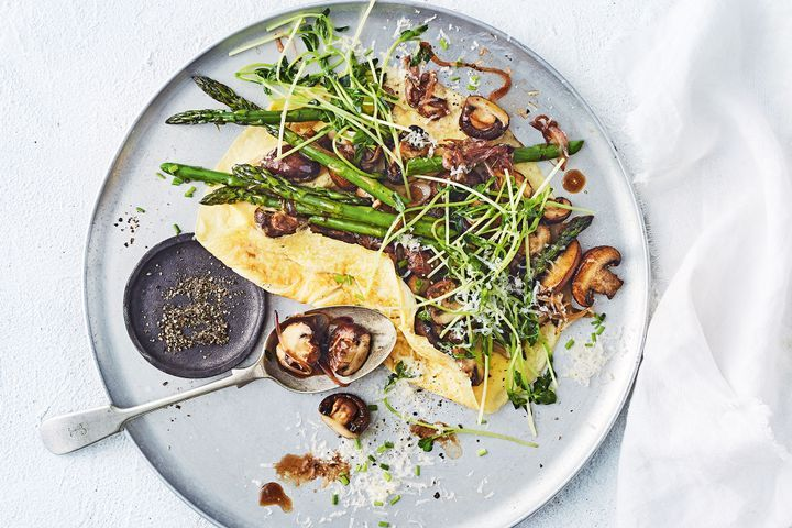 A mushroom & asparagus omelette served on a plate.