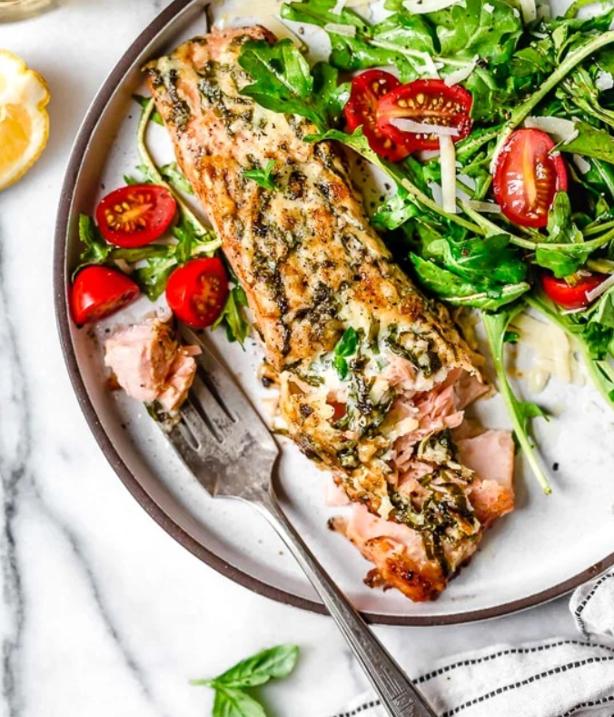 Salmon fillet with Parmesan and basil crust served on a plate with salad.