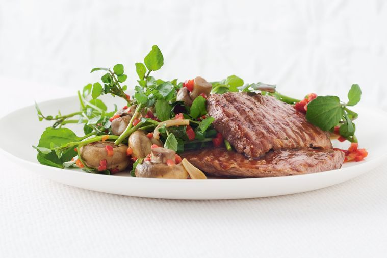 Lamb with marinated mushrooms on a plate served with watercress sprigs